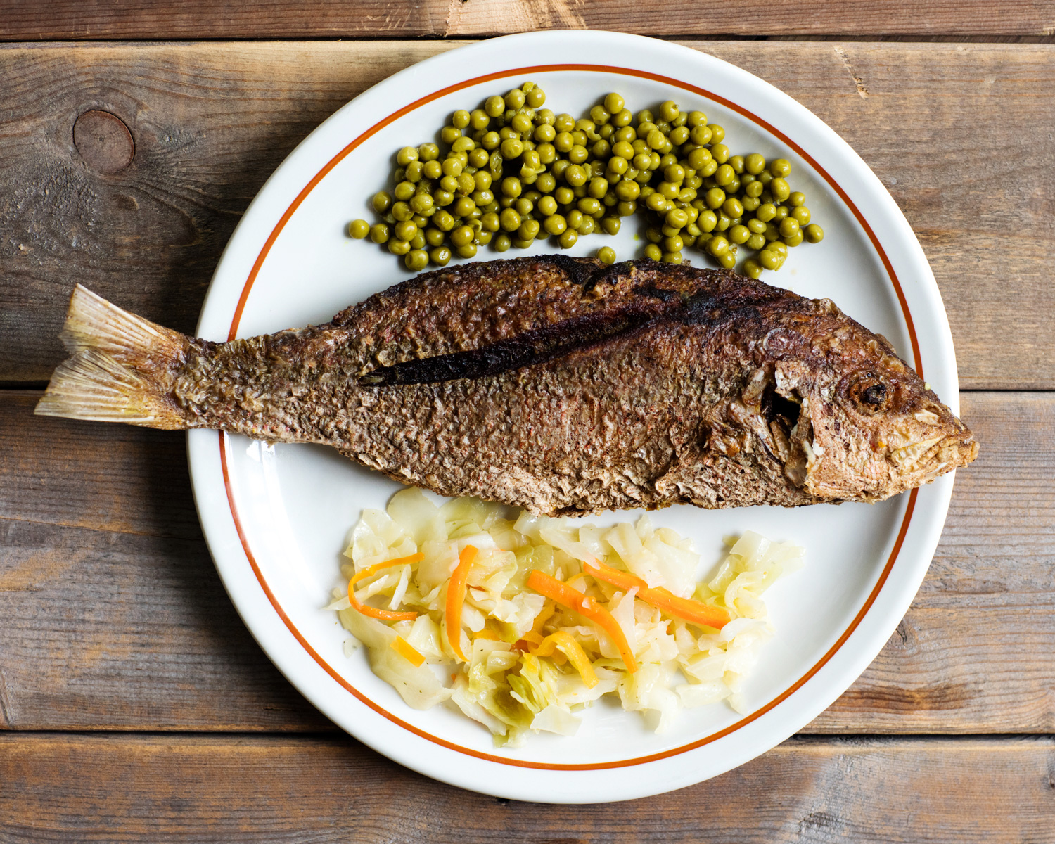 Whole fried fish with peas on plate