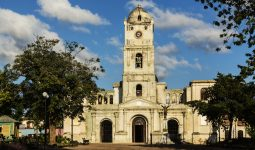 """Church tower and plaza under blue sky, Holguin, Holguin, Cuba"""