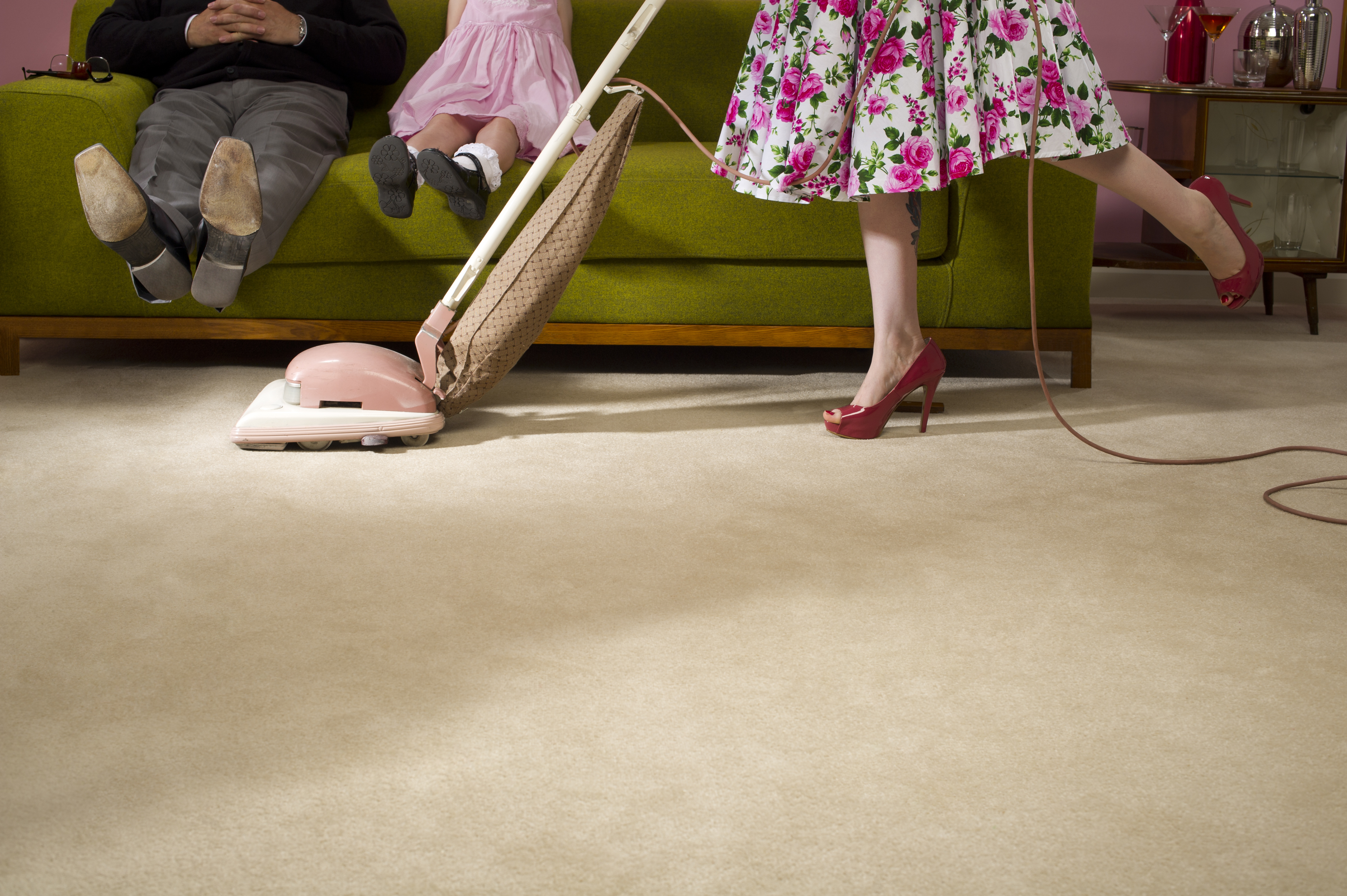 Housewife hoovers under the family trying to keep her copy space clean