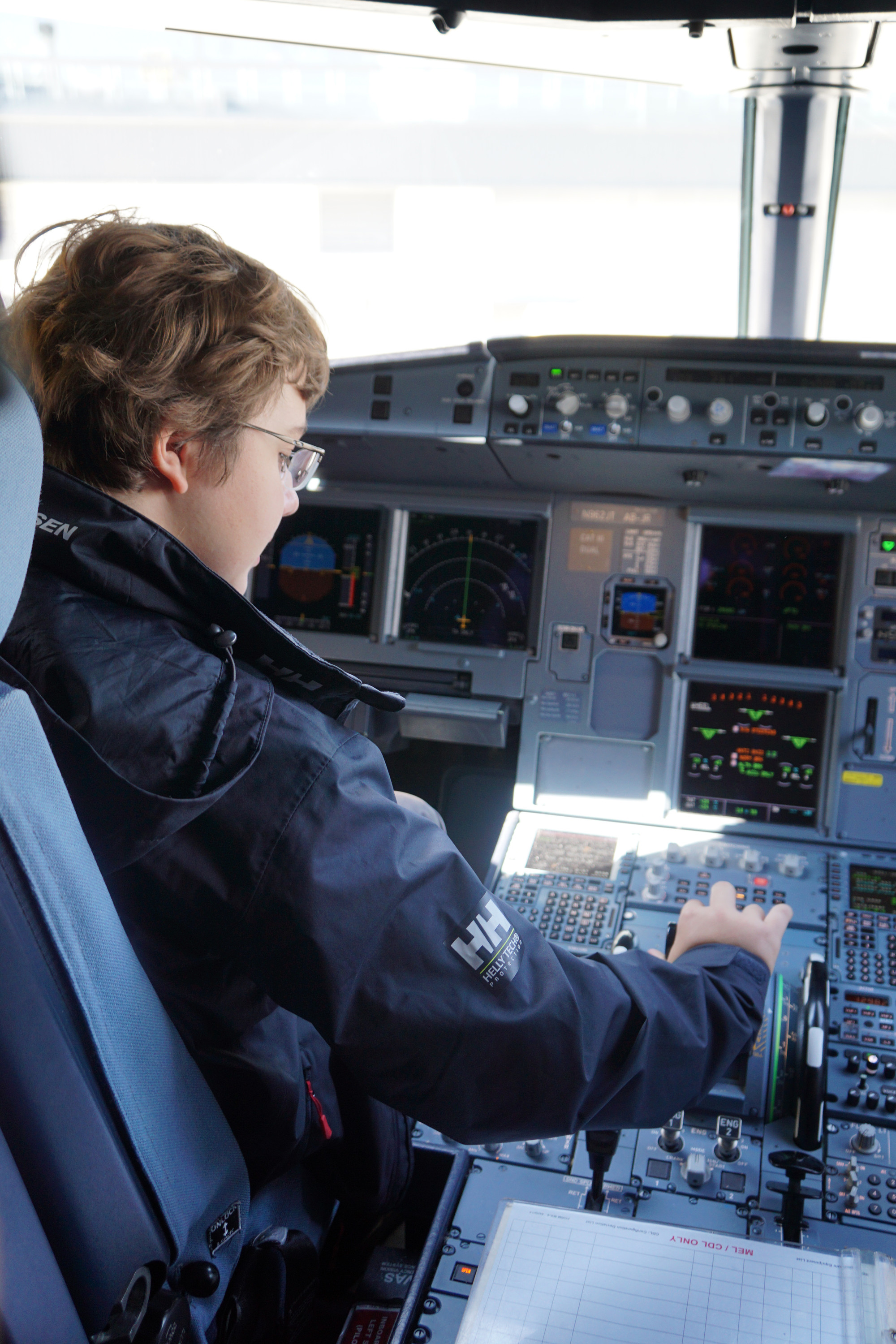 An aspiring pilot examines the cockpit of a JetBlue A320