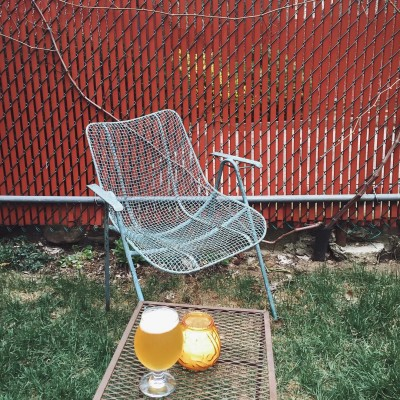 Exterior metal chair with chain link fence and drink