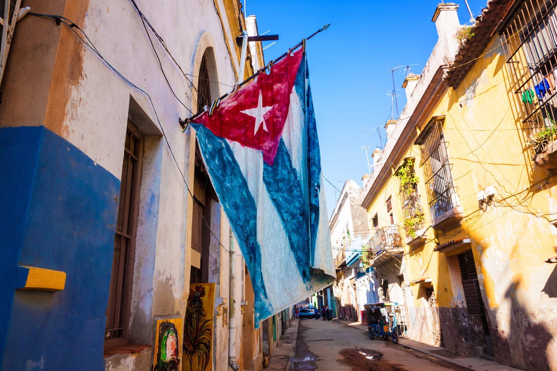 Street sidelined by decaying buildings in Old Havana with a big cuban flag; Shutterstock ID 112151150; name: Chan Tran; Client: Jetblue; Publication: Blog; Story ID: n/a
