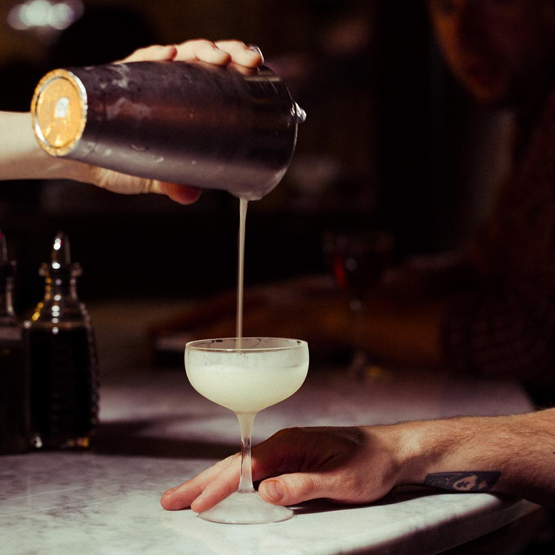 Hand pouring cocktail into glass at bar
