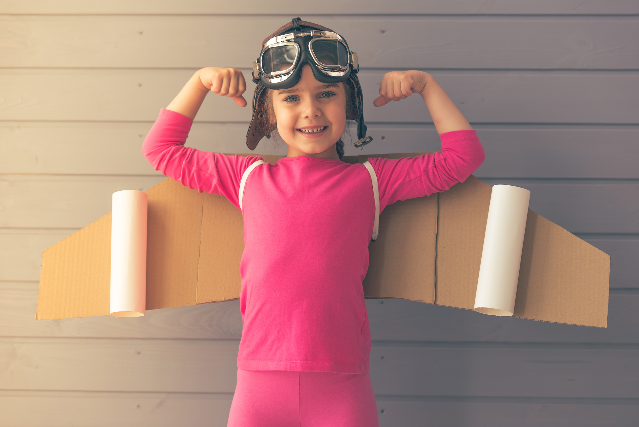 Cute little girl dressed like a pilot with toy wings is showing her muscles, smiling and looking at camera, against gray wall