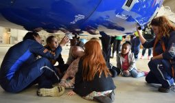 Kids sitting underneath airplane