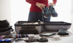 Woman packing suitcase, holding trainers, mid section