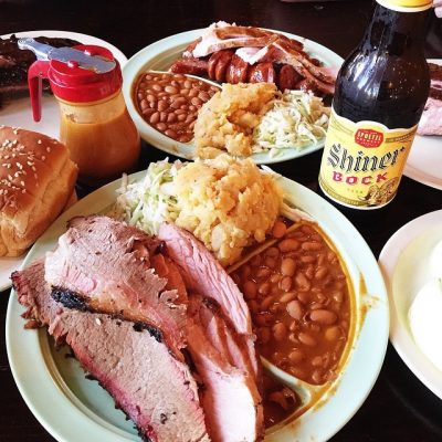 Plates of BBQ meat with beans and beer