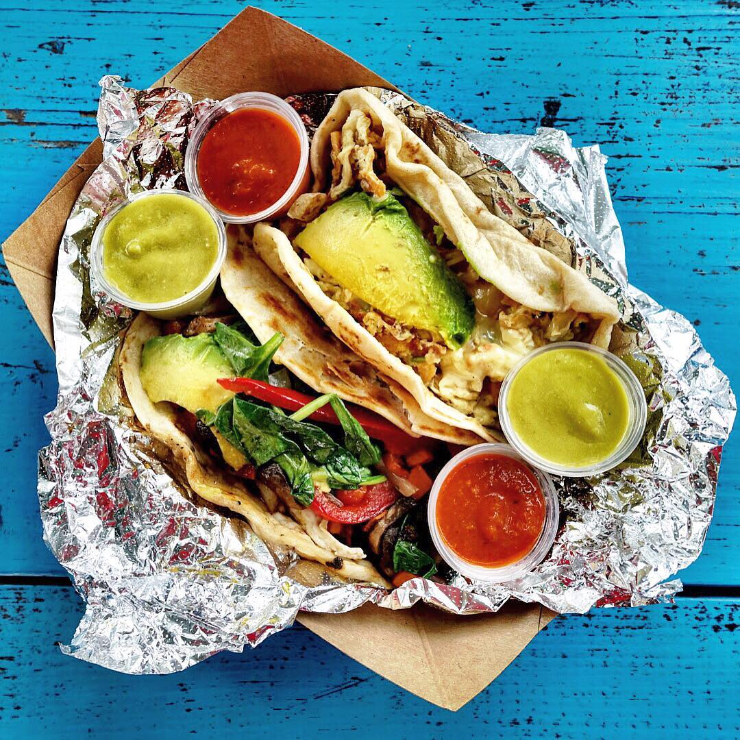 Street tacos in foil with red and green sauce
