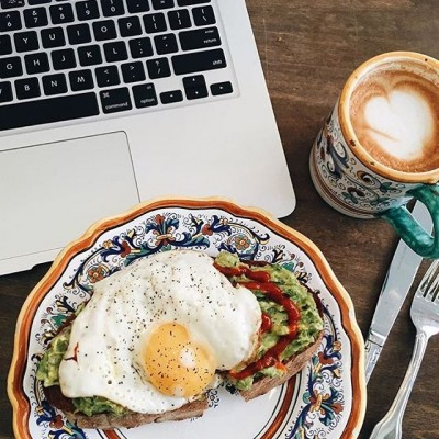 Open egg sandwich with coffee and laptop