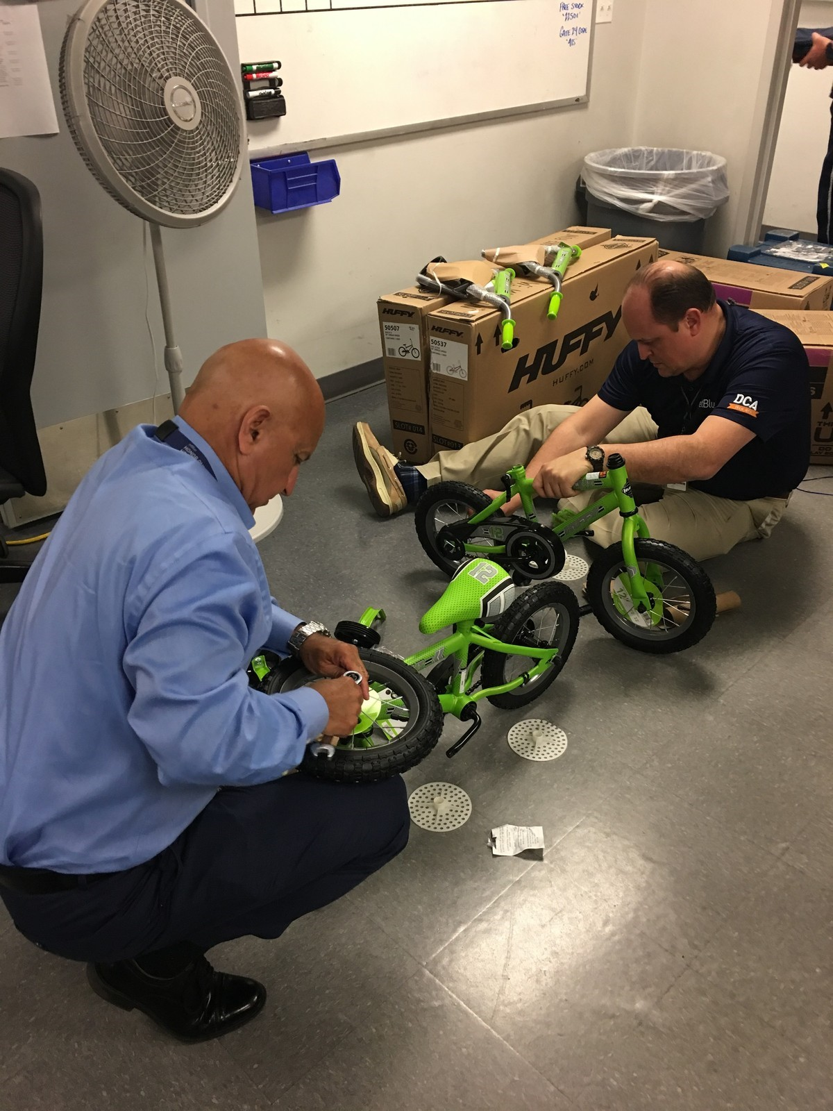 Crewmembers work on assembling a bike