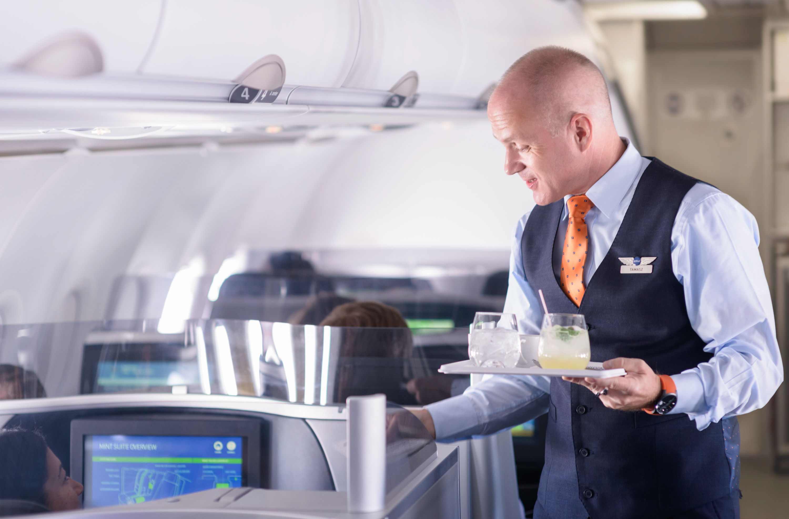 Man serving drinks on airplane